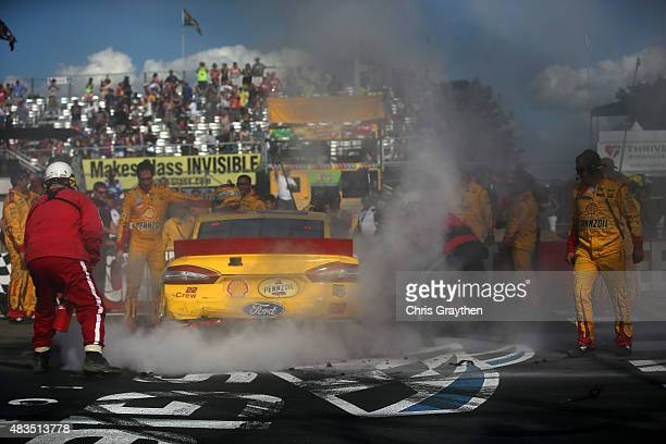Crew members of Joey Logano driver of the Shell Pennzoil Ford put out a fire on his car after celebrating with a burnout after winning the NASCAR...