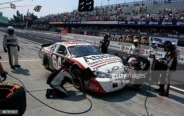 Crew members of Max Papis driver of the Atreus Homes and Communities Chevrolet work to repair damage suffered during the NASCAR Nationwide Series...