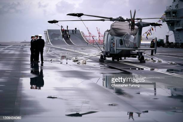 Crew members of Royal Navy aircraft carrier HMS Prince of Wales walk on the flight deck as she berths at Liverpool's cruise terminal on February 29...