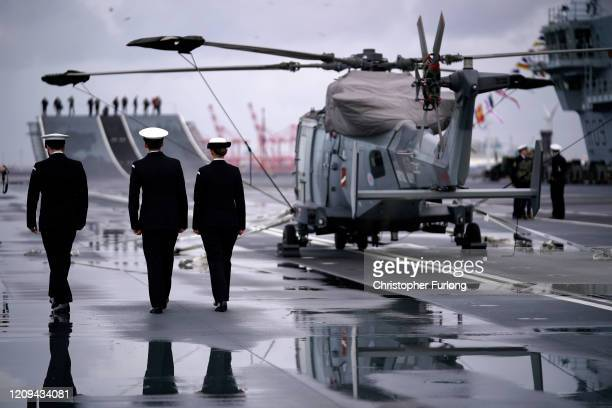 Crew members of Royal Navy aircraft carrier, HMS Prince of Wales, walk on the flight deck as she berths at Liverpool's cruise terminal on February...