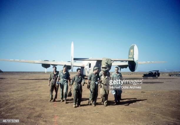 Crew members of the 44th Bombardment Group walk to base with B24 Liberator in the background at the US Air Force Base in Benghazi Libya
