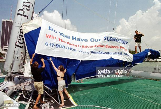 "Crew members of the 86-foot catamaran ""Explorer"" help bring down a banner 29 May 1999 placed by skipper Cam Lewis on the cover of the mainsail asking..."