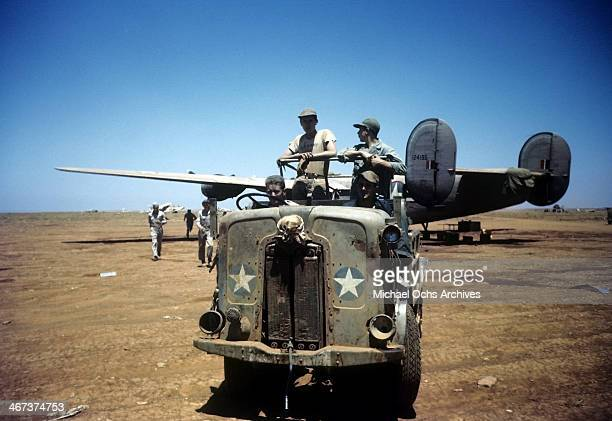 Crew members of the 98th Bombardment Group drive back to the base as a B24 Liberator sits in the background at the US Air Force Base in Benghazi Libya