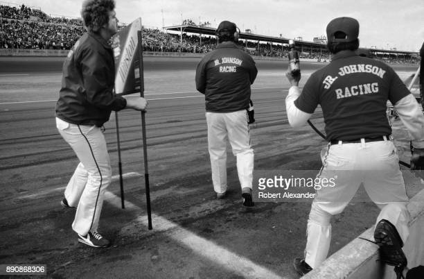 Crew members of the Junior Johnson Racing team snap into action as the team's driver Cale Yarborough comes in for a pit stop during the running of...