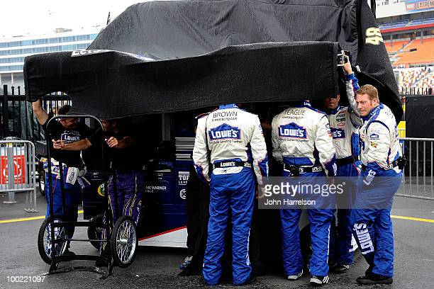 Crew members of the Lowe's Chevrolet stand under cover in the garage area as rain falls to delay qualifying for the NASCAR Sprint Cup Series AllStar...