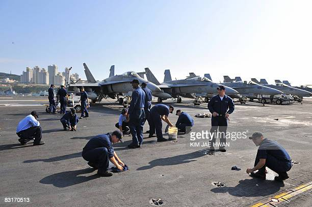 Crew members of the USS CVN 73 George Washington aircraft carrier clean the flight deck at the naval base port in Busan on October 8 2008 The USS...
