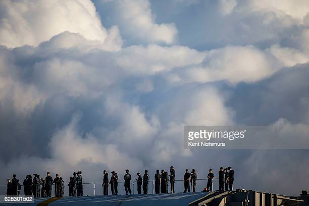 Crew members of the USS John C Stennis stand on deck as the guided missile destroyer USS Halsey performs a PassinReview during a ceremony...