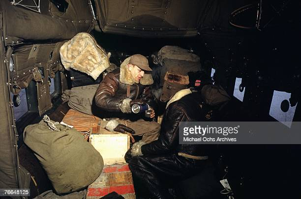 Crew members on a B24 Liberator Express cargo plane share a cup of coffee on route to a United States Army Air Force base in December 1942 in Goose...