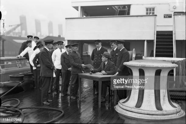 Crew members on board the Cunard liner RMS Aquitania, receiving forms to enable them to vote by proxy in the forthcoming UK general election,...