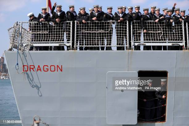 Crew members onboard HMS Dragon wave to the waiting crowd as she returns to Portsmouth Naval Base after a sevenmonth Gulf mission