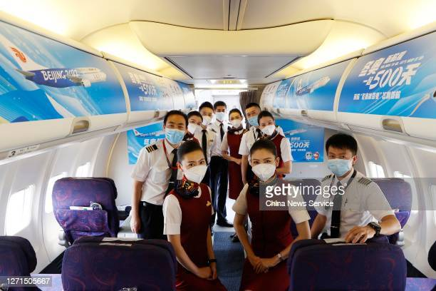 Crew members pose for photos on a newly painted Boeing 737 aircraft of Air China with patterns of the emblems and mascots of Beijing 2022 Winter...