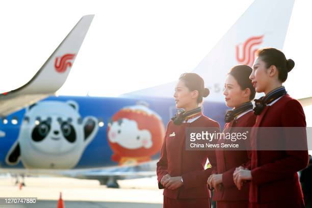 Crew members pose in front of a newly painted Boeing 737 aircraft of Air China with patterns of the emblems and mascots of Beijing 2022 Winter...