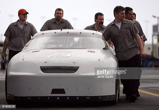 Crew members push a car driven by Dale Earnhardt Jr to inspection in the garage area during NASCAR NEXTEL Cup testing at the Daytona International...
