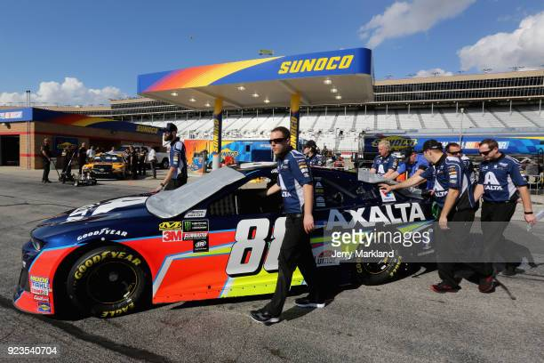 Crew members push the car of Alex Bowman driver of the Axalta Chevrolet towards the grid during qualifying for the Monster Energy NASCAR Cup Series...