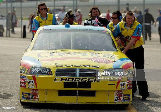 Crew members push the car of Bobby Labonte driver of the Cheerios/Betty Crocker Dodge in the garage area during practice for the NASCAR Sprint Cup...