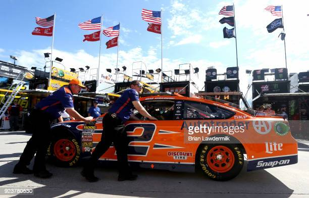 Crew members push the car of Brad Keselowski driver of the Autotrader Ford through the garage area during practice for the Monster Energy NASCAR Cup...