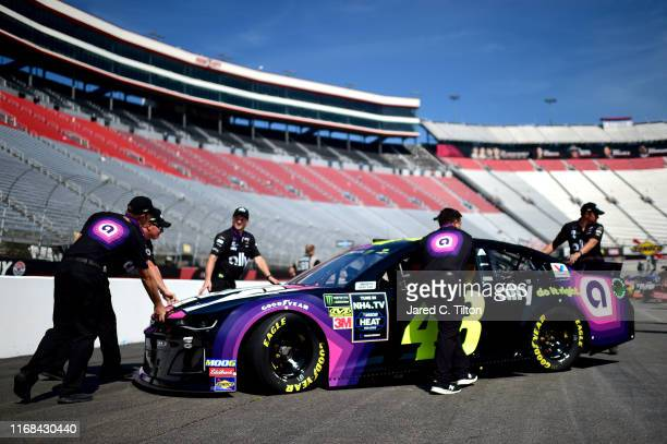 Crew members push the car of Jimmie Johnson driver of the Ally Chevrolet through the garage during practice for the Monster Energy NASCAR Cup Series...