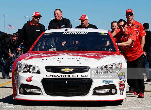Crew members push the car of Kevin Harvick driver of the Budweiser/Jimmy John's Chevrolet during practice for the 57th Annual Daytona 500 at Daytona...