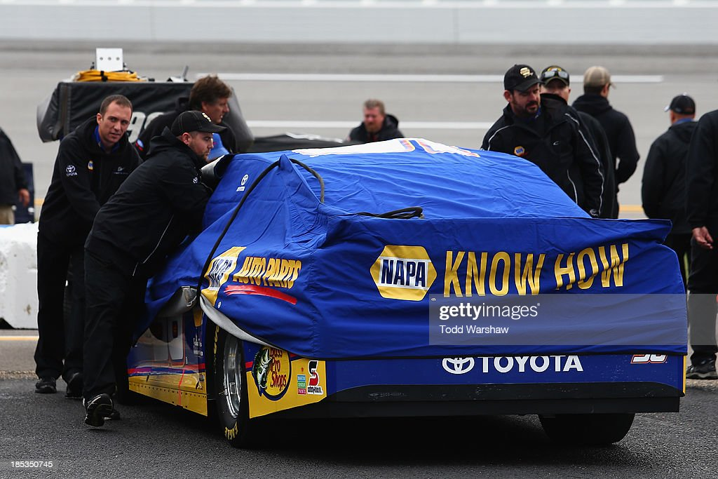Crew members push the car of Martin Truex Jr., driver of the #56 NAPA Auto Parts Toyota, back to the garage after rain cancelled qualifying for the NASCAR Sprint Cup Series 45th Annual Camping World RV Sales 500 at Talladega Superspeedway on October 19, 2013 in Talladega, Alabama.