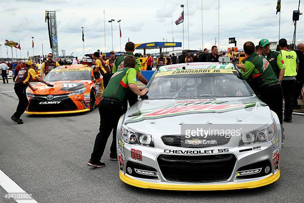 Crew members push the cars of Dale Earnhardt Jr driver of the Diet Mountain Dew Chevrolet and Kyle Busch driver of the MM's Halloween Toyota on the...