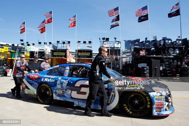 Crew members push the DOW Energy Water Chevrolet through the garage area during practice for the Monster Energy NASCAR Cup Series O'Reilly Auto Parts...