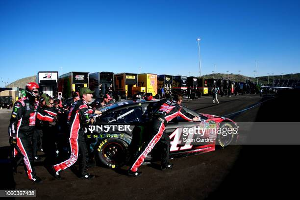 Crew members push the Haas Automation/Monster Energy Ford driven by Kurt Busch through the garage area following the Monster Energy NASCAR Cup Series...