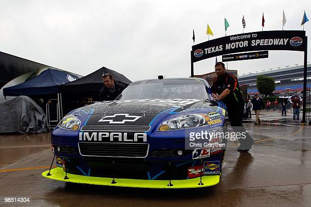 Crew members push the Hendrickcars.com Chevrolet, driven by Mark Martin, through the garage area as rain delays practice for the NASCAR Sprint Cup...