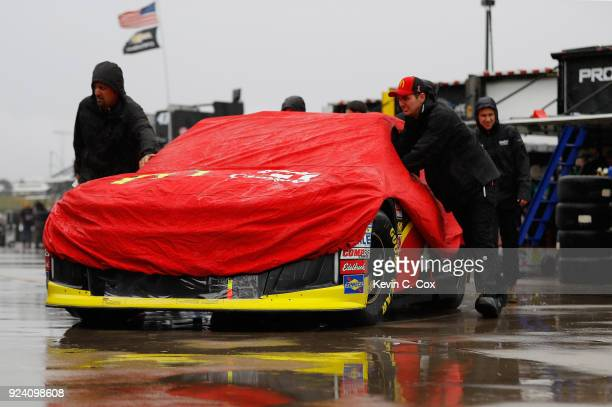 Crew members push the McDonald's Chevrolet driven by Jamie McMurray through the garage area during the Monster Energy NASCAR Cup Series Folds of...