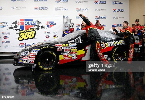 Crew members push the Misscosukee Indian Gaming and Resort Chevrolet driven by Mike Bliss after Bliss was awarded the win due to weather conditions...