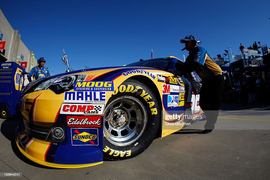 Crew members push the NAPA Auto Parts Toyota of Martin Truex