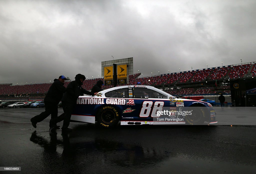 Crew members push the #88 National Guard Chevrolet, driven by Dale Earnhardt Jr., through the garage area as rain delayed qualifying for the NASCAR Sprint Cup Series Aaron's 499 at Talladega Superspeedway on May 4, 2013 in Talladega, Alabama. Sprint Cup qualifying was officially canceled due to inclimate weather.