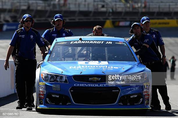 Crew members push the Nationwide Chevrolet driven by Dale Earnhardt Jr through the garage area during practice for the NASCAR Sprint Cup Series Food...