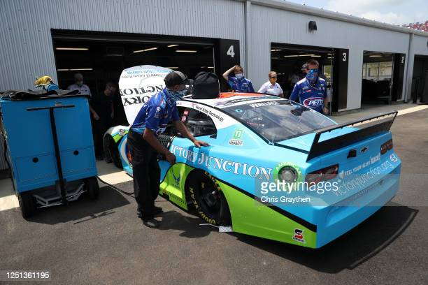 Crew members push the Victory Junction Chevrolet driven by Bubba Wallace through the garage area prior to the NASCAR Cup Series GEICO 500 at...