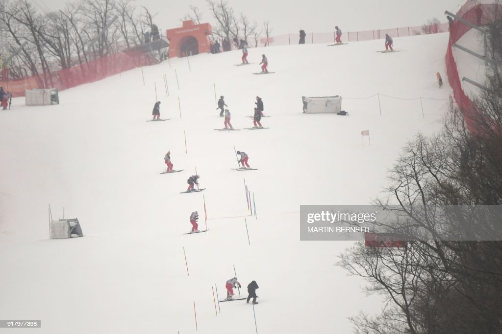 TOPSHOT - Crew members remove snow poles after the Alpine Skiing Women's Slalom was cancelled due to weather conditions at the Jeongseon Alpine Center during the Pyeongchang 2018 Winter Olympic Games in Pyeongchang on February 14, 2018. / AFP PHOTO / Martin BERNETTI