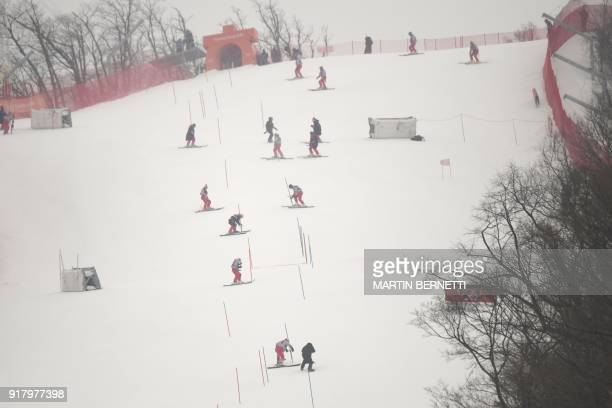 TOPSHOT Crew members remove snow poles after the Alpine Skiing Women's Slalom was cancelled due to weather conditions at the Jeongseon Alpine Center...