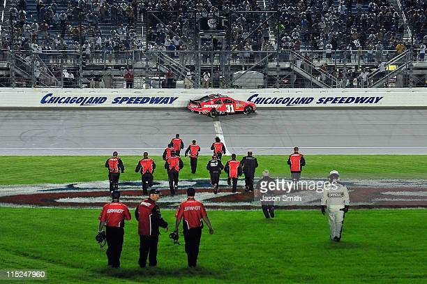 Crew members run across the infield to congratulate Justin Allgaier driver of the Brandt Chevrolet after he won the NASCAR Nationwide Series STP 300...