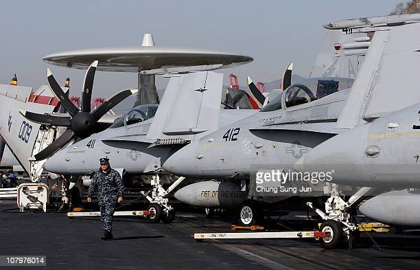 Crew members stand on the flight deck of Aircraft Carrier USS Carl Vinson whilst at anchor in Busan port on January 11 2011 in Busan The USS Carl...