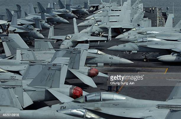 Crew members stand on the flight deck of Aircraft Carrier USS George Washington whilst at anchor in Busan port on July 11 2014 in Busan South Korea...