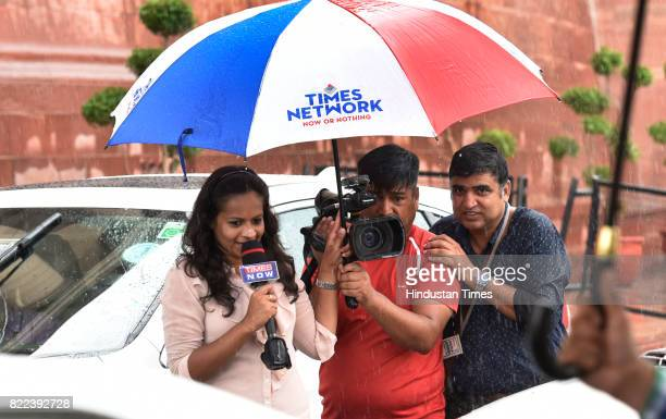 TV crew members stand under an umbrella as they report in the heavy down pour after swearingin ceremony of President Ram Nath Kovind at Parliament on...
