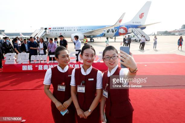 Crew members take a selfie in front of a newly painted Boeing 737 aircraft of Air China with patterns of the emblems and mascots of Beijing 2022...