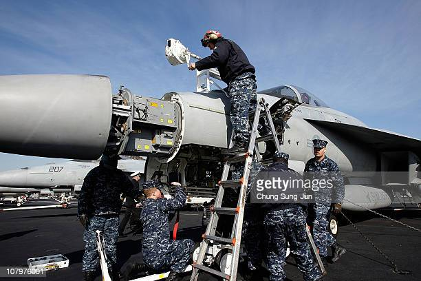 Crew members tend to an F/A 18 Hornet aircraft on the flight deck of Aircraft Carrier USS Carl Vinson whilst at anchor in Busan port on January 11...