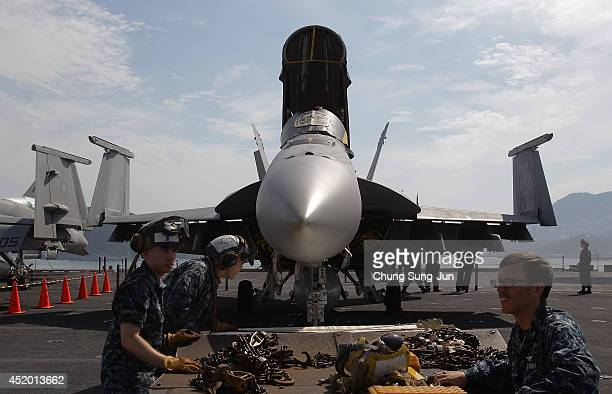 Crew members tend to an F/A 18 Hornet aircraft on the flight deck of Aircraft Carrier USS George Washington whilst at anchor in Busan port on July 11...