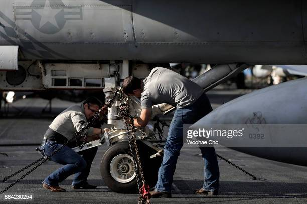 Crew members tend to an F/A18 E/F Super Hornet on the deck of the US aircraft carrier Ronald Reagan on October 21 2017 in Busan South Korea The...