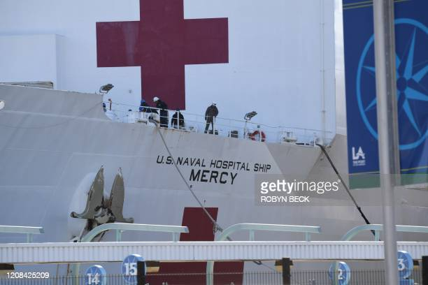 Crew members throw out a line to dock as the US Navy hospital ship Mercy arrives March 27 2020 at the Port of Los Angeles to help local hospitals...