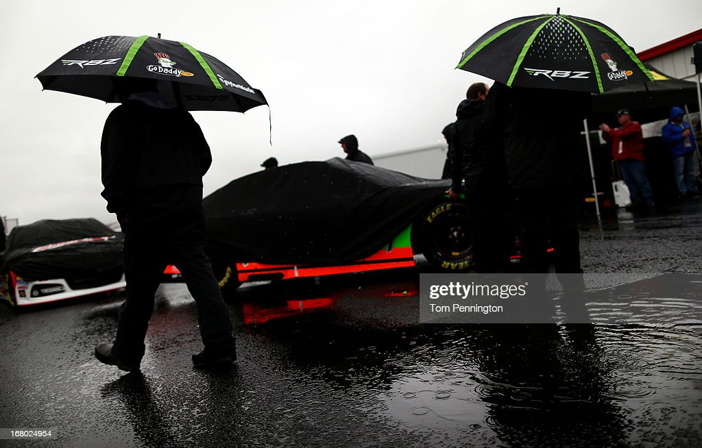 Crew members wait with the #10 GoDaddy.com Chevrolet, driven by Danica Patrick, in the garage area as rain delayed qualifying for the NASCAR Sprint Cup Series Aaron's 499 at Talladega Superspeedway on May 4, 2013 in Talladega, Alabama. Sprint Cup qualifying was officially canceled due to inclimate weather.