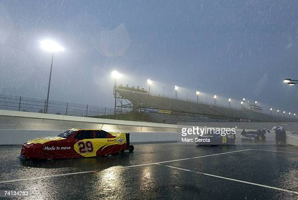 Crew members watch over the race cars on pit road during heavy rain, prior to the NASCAR Nextel Cup Series Dodge Avenger 500 on May 12, 2007 at...