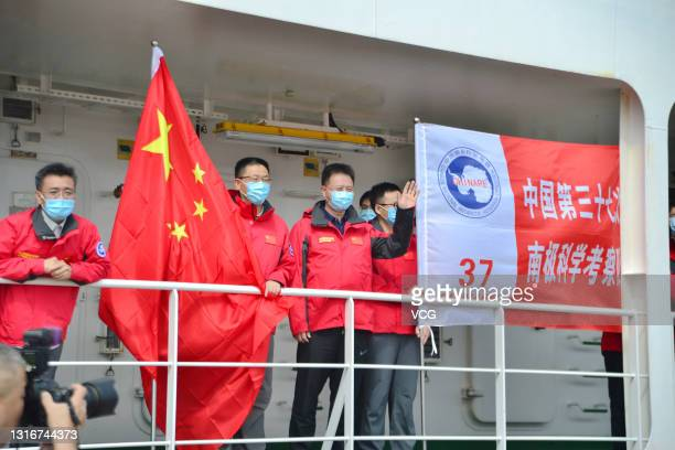 Crew members wave as China's research icebreaker Xuelong 2, or Snow Dragon 2, arrives at Waigaoqiao port after over 5-month Antarctic expedition on...