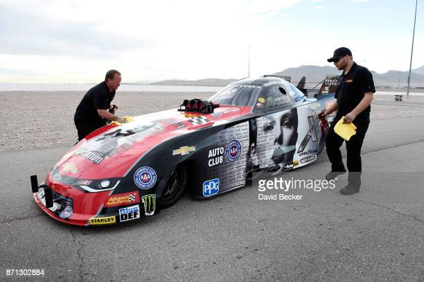 Crew members wipe down NHRA Funny Car driver Courtney Force's Advance Auto Parts Chevrolet Camaro SS funny car as it is seen featuring the cover of...