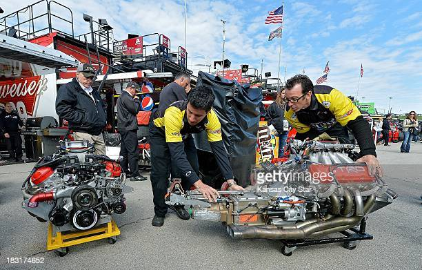 Crew members with Sprint Cup Series driver Kyle Busch exchange engines from the primary car to the backup car after Busch hit the wall during a...