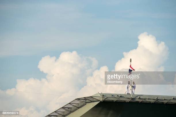 Crew members work on a pole flying the Thai national flag aboard the Royal Thai Navy's HTMS Chakri Narubet P/N 911 aircraft carrier at the IMDEX Asia...